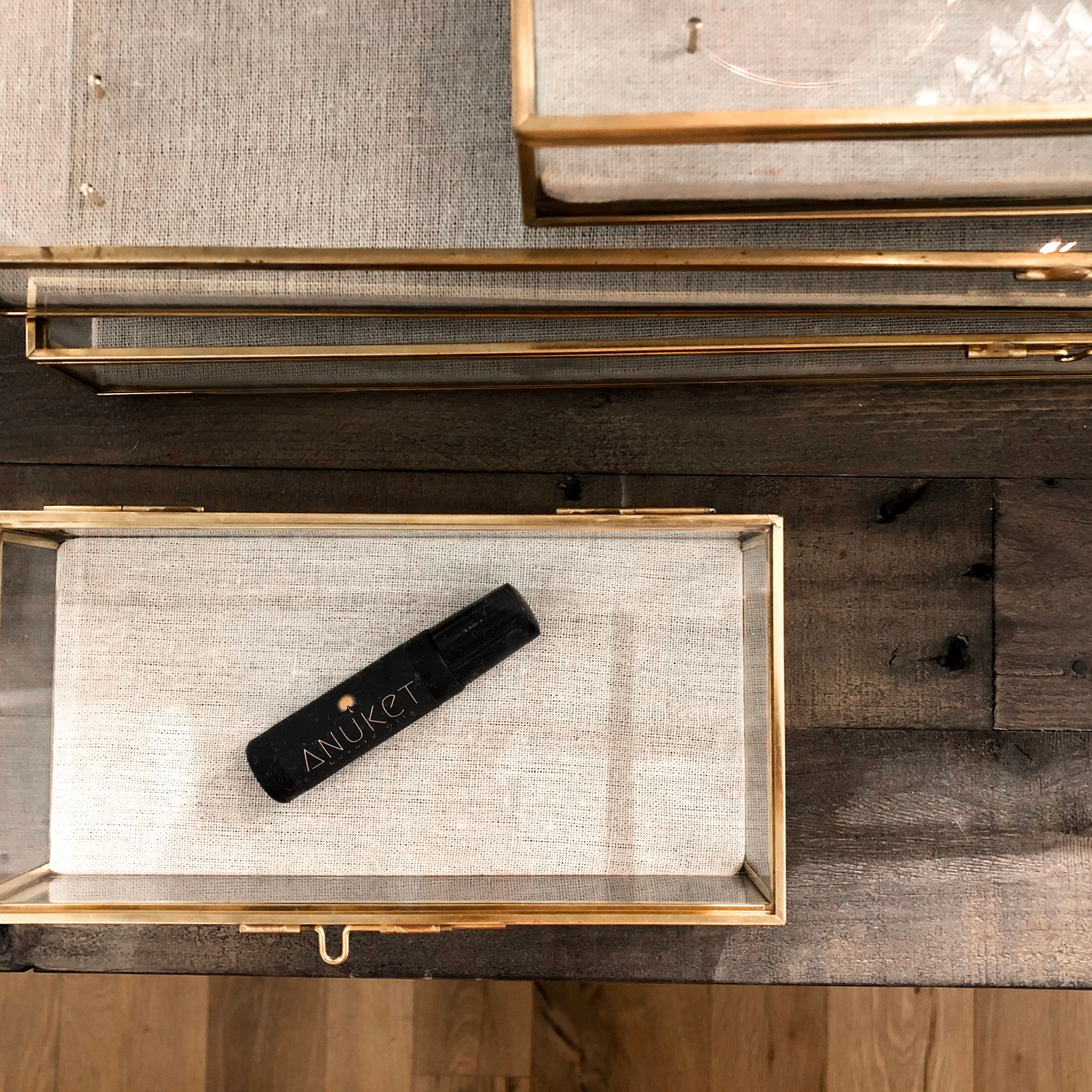 Bottle of essential oil fragrance by Anuket Luxury Oils in a glass box on a wooden tabletop