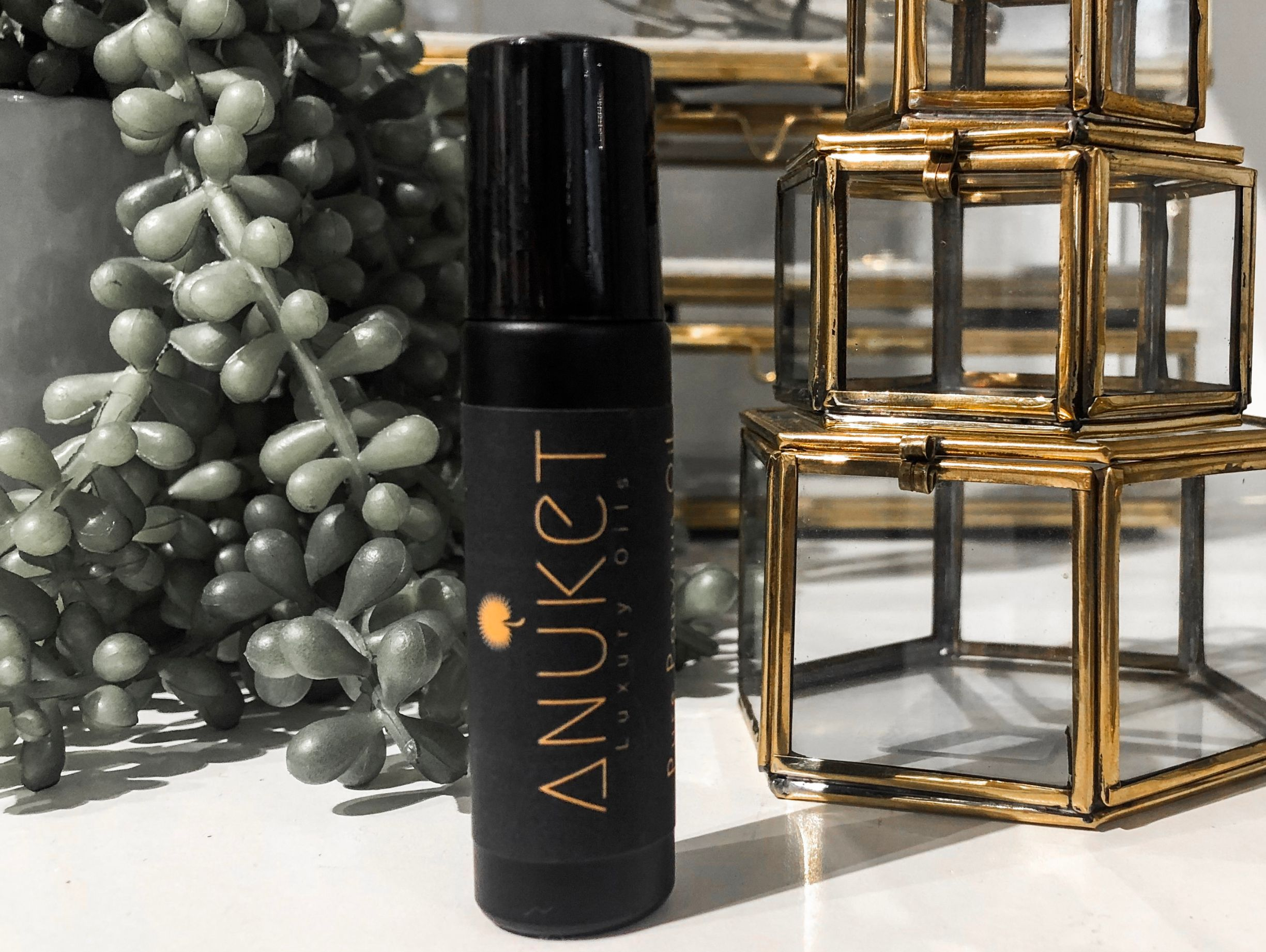 photo of Anuket Luxury Apothecary's Signature Scent in a matte black rollerball container, sitting on a marble tile with a gold fixture surrounded by greenery