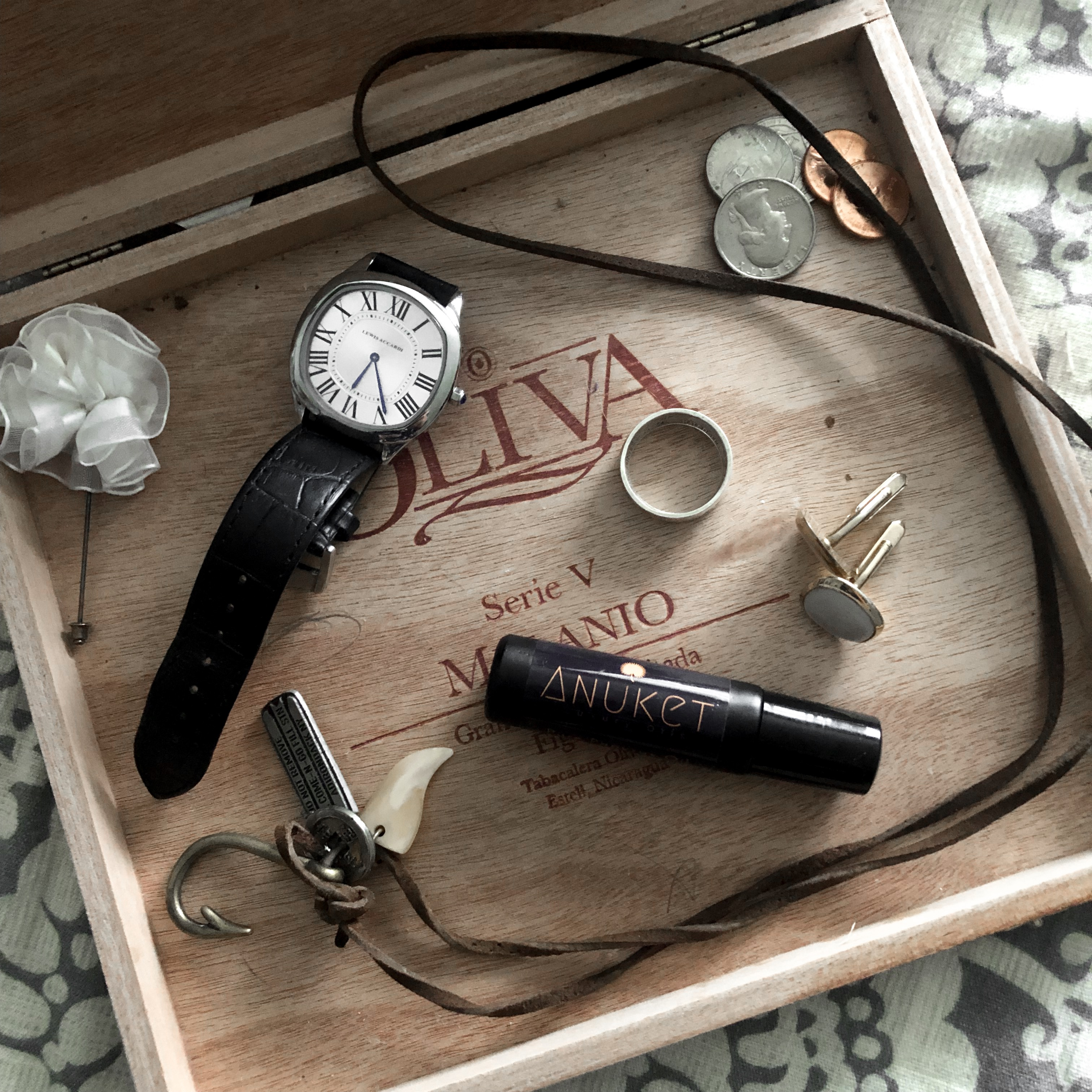 Anuket matte black rollerball in a wooden keepsake box surrounded by a leather pendant, a watch, coins, and other knick knacks