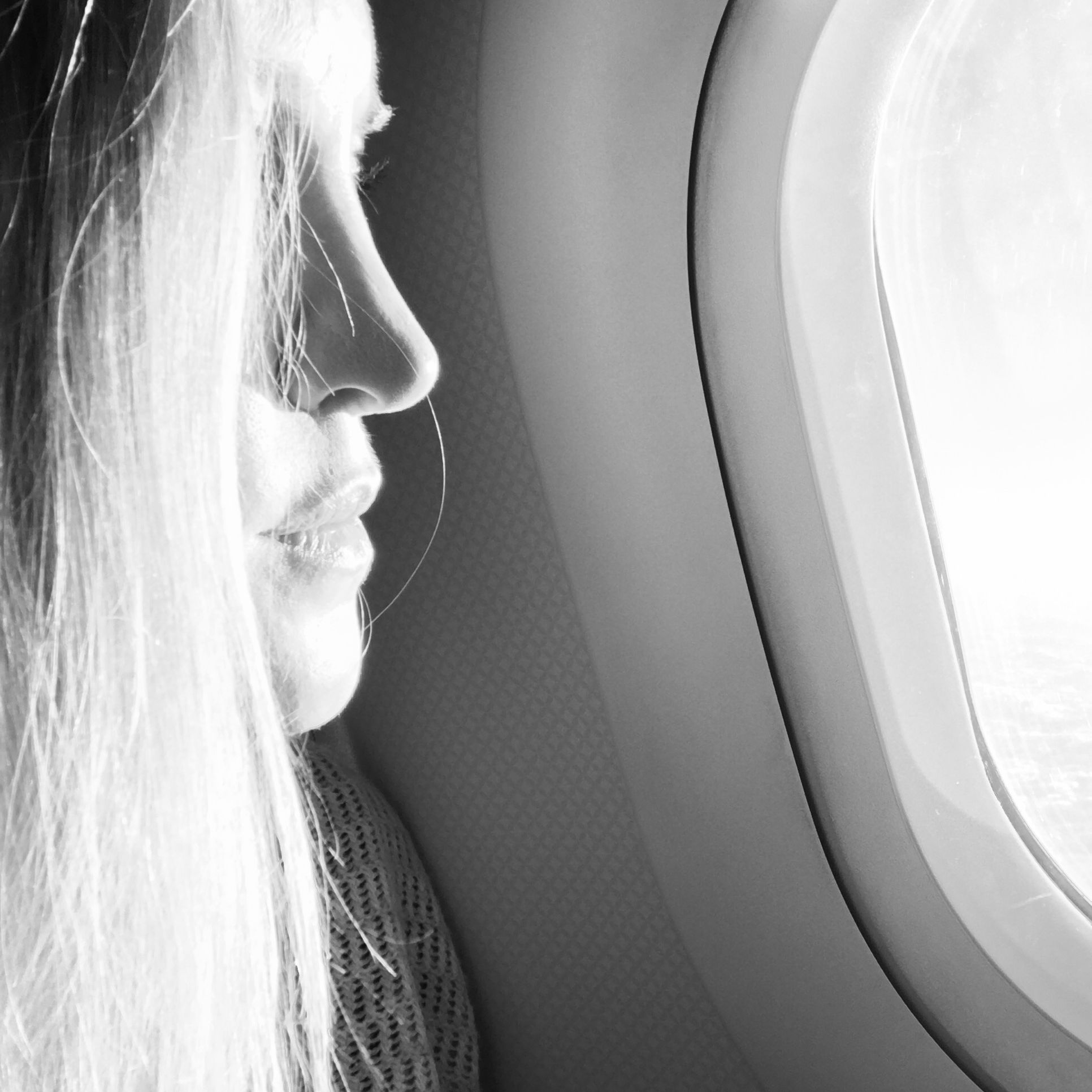Black and white image of Ashlee Dozier, Owner of Anuket Luxury Apothecary, in flight looking out of the airplane window. Link to blog post.