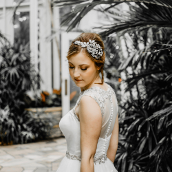 Photo of a Bride walking down a path, surrounded by greenery, with lots of pearl accents on her hair piece and dress