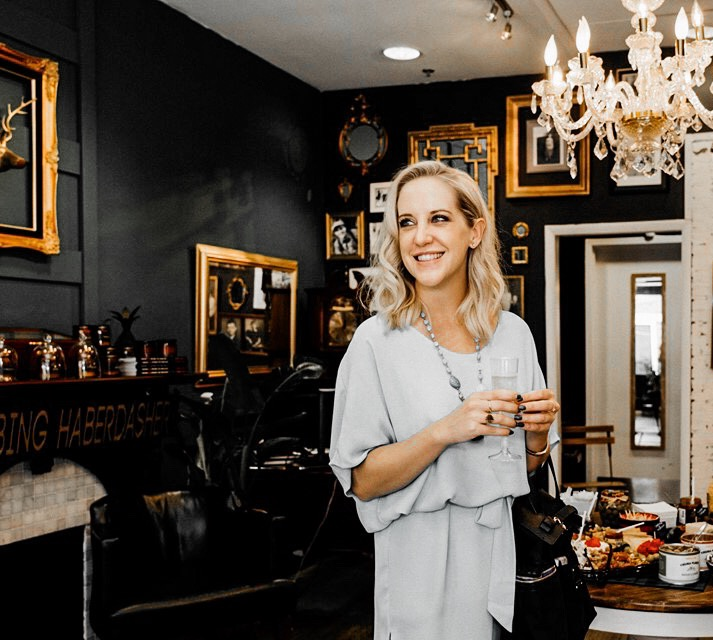 Image of Anuket Luxury Apothecary Owner, Ashlee Dozier holding a glass of champagne and smiling
