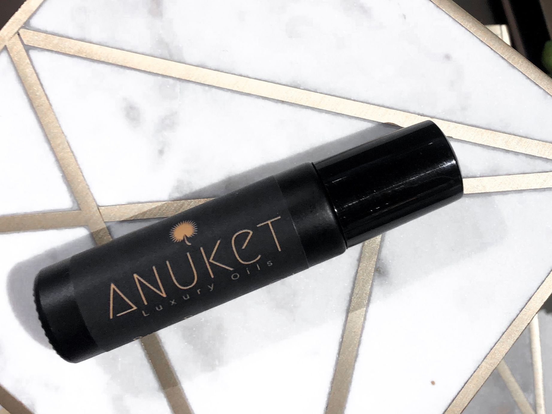 photo of Anuket Luxury Apothecary's Signature Scent on a gold and marble tile linking to blog with 5 helpful tips to make fragrance last longer