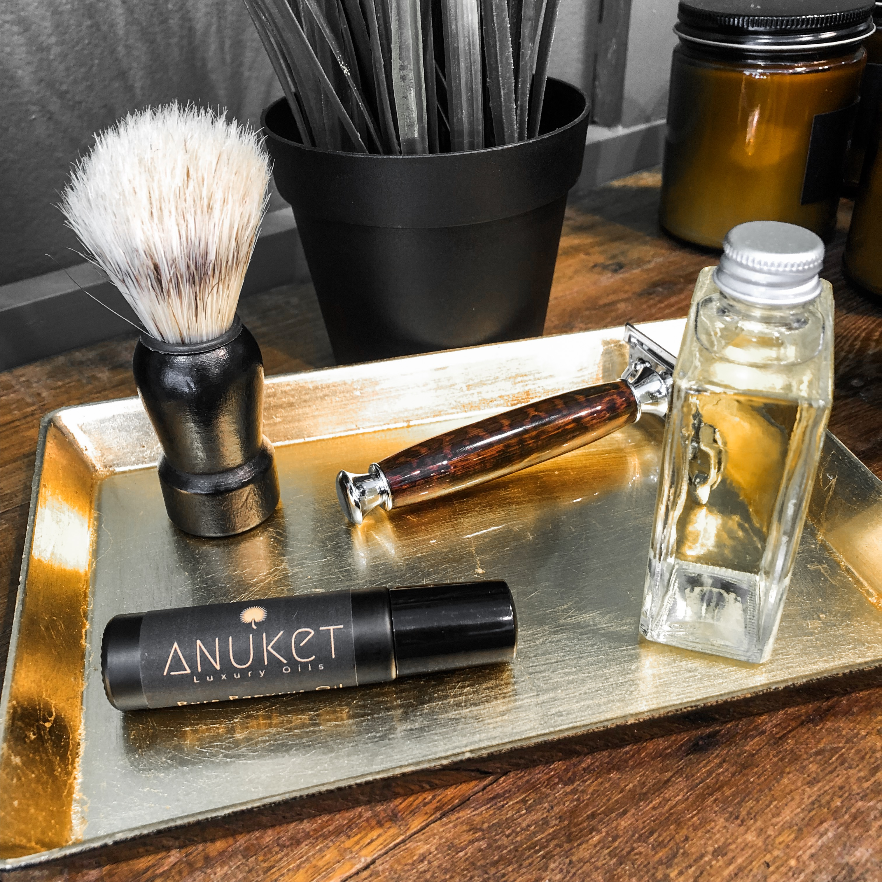 Golden tray with Anuket roll-on fragrance bottle, safety razor, aftershave, and shave brush.