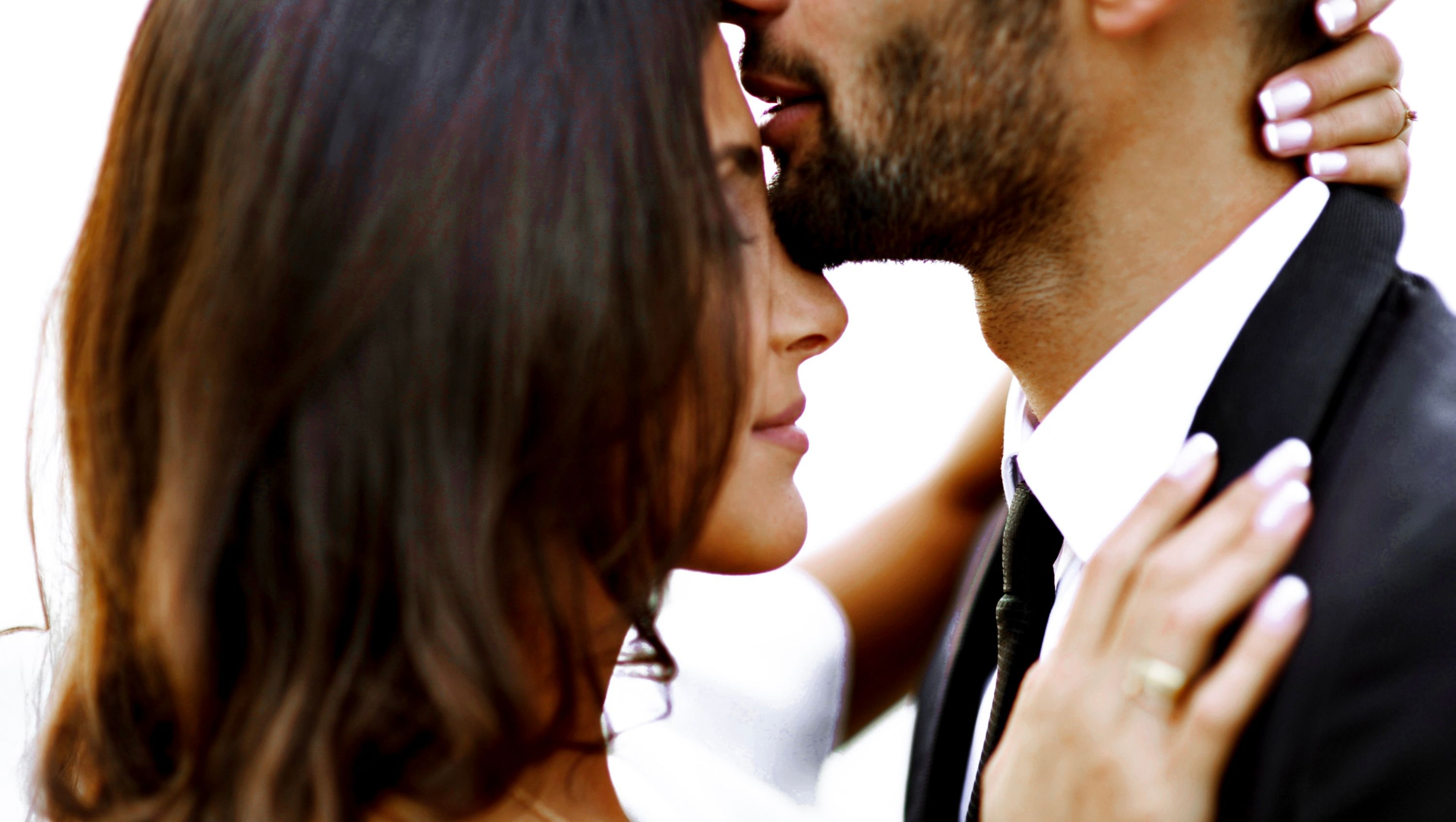 photo of a man with a goatee kissing the forehead of a brunette woman on in a very sweet and intimate embrace