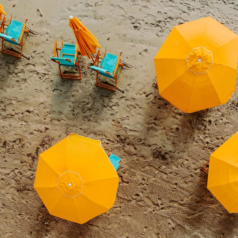 tropical home decor ideas and warm color trends with yellow beach umbrellas and beach chairs by Annie Sprat