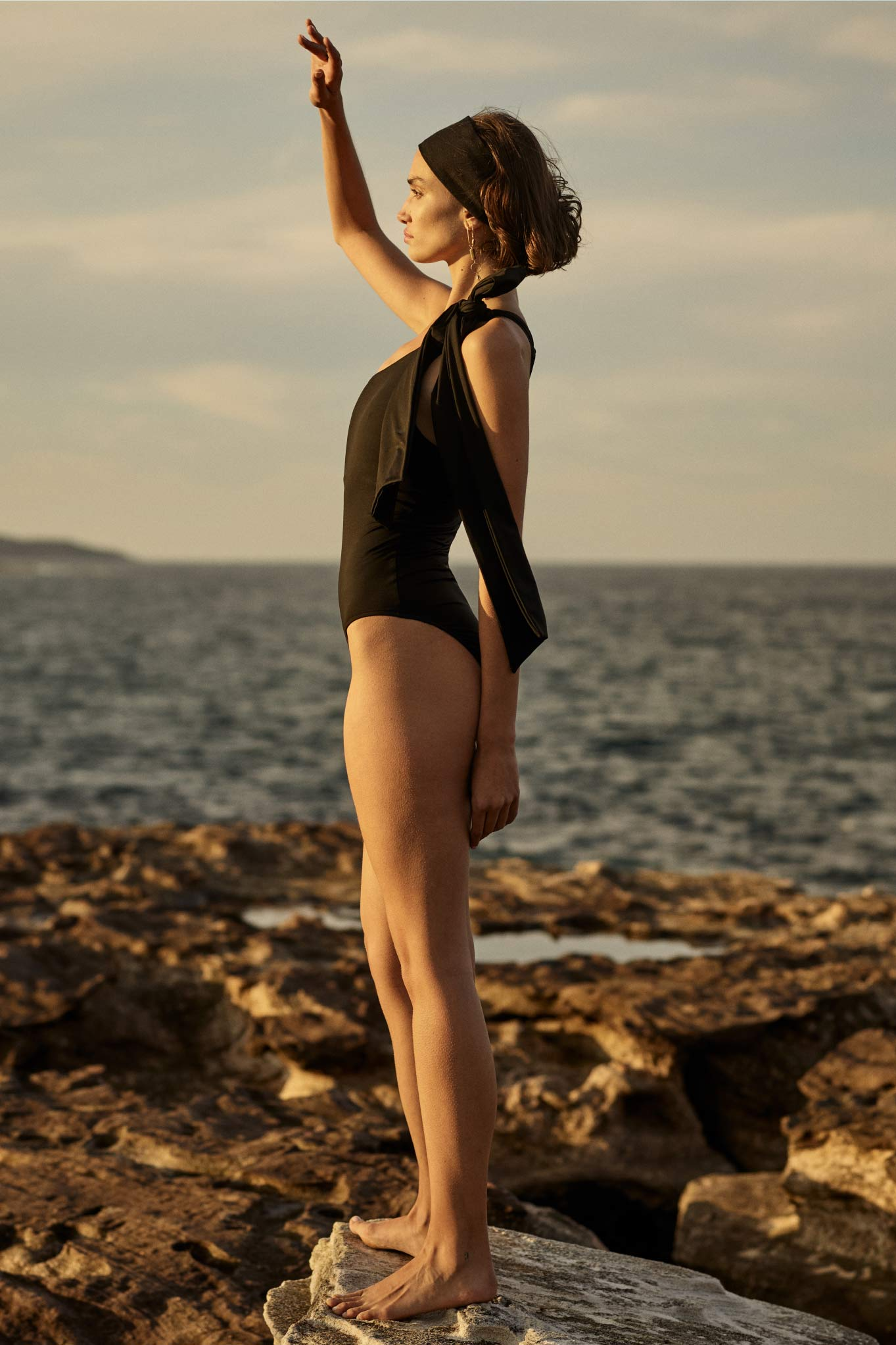 BOND BORN Australian designer swimwear collection includes the Clementine One Shoulder One Piece Swimsuit in Black with over sized knot .