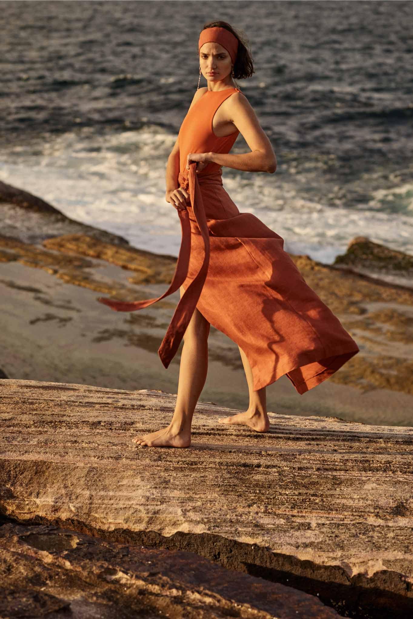 BONDI BORN Australian Designer Swim and Resort Wear featuring this rust linen skirt and luxury italian lycra one piece swimsuit in orange.
