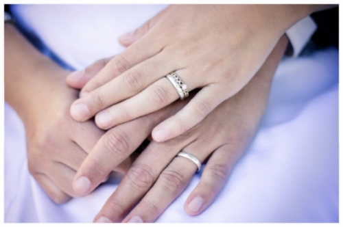 Engaged Couple Holding Hands While Wearing Wedding Bands