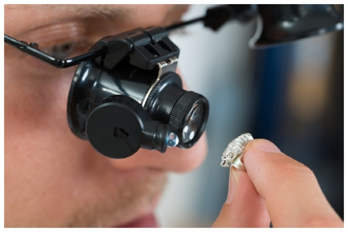 Qualified Jeweler Inspecting to See if a Diamond is Real