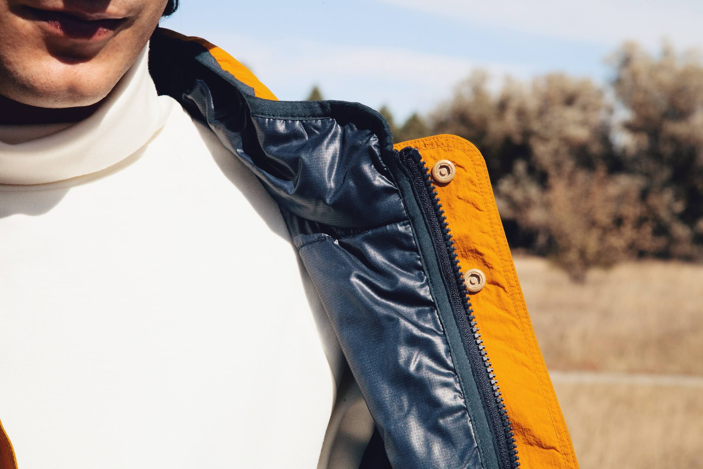 nanamica reversible insulation jacket and turtleneck on body