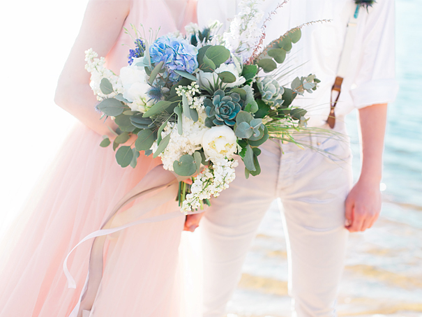 Beach wedding featuring dusty rose and emerald green florals