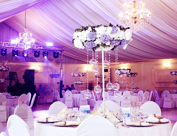White, lavender, and victorian lilac indoor wedding reception with uplighting and tall floral crystal centerpieces