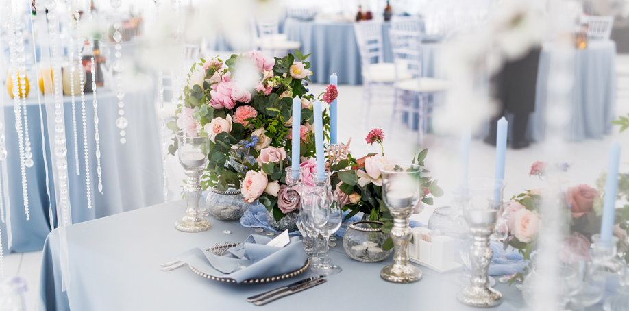 Dusty blue wedding reception table setting with napkin, charger plate, and flower arrangement