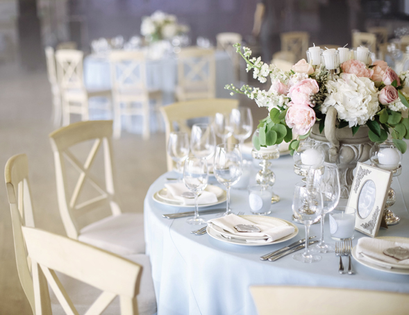Dusty blue rustic wedding reception inside barn with place setting and floral centerpiece