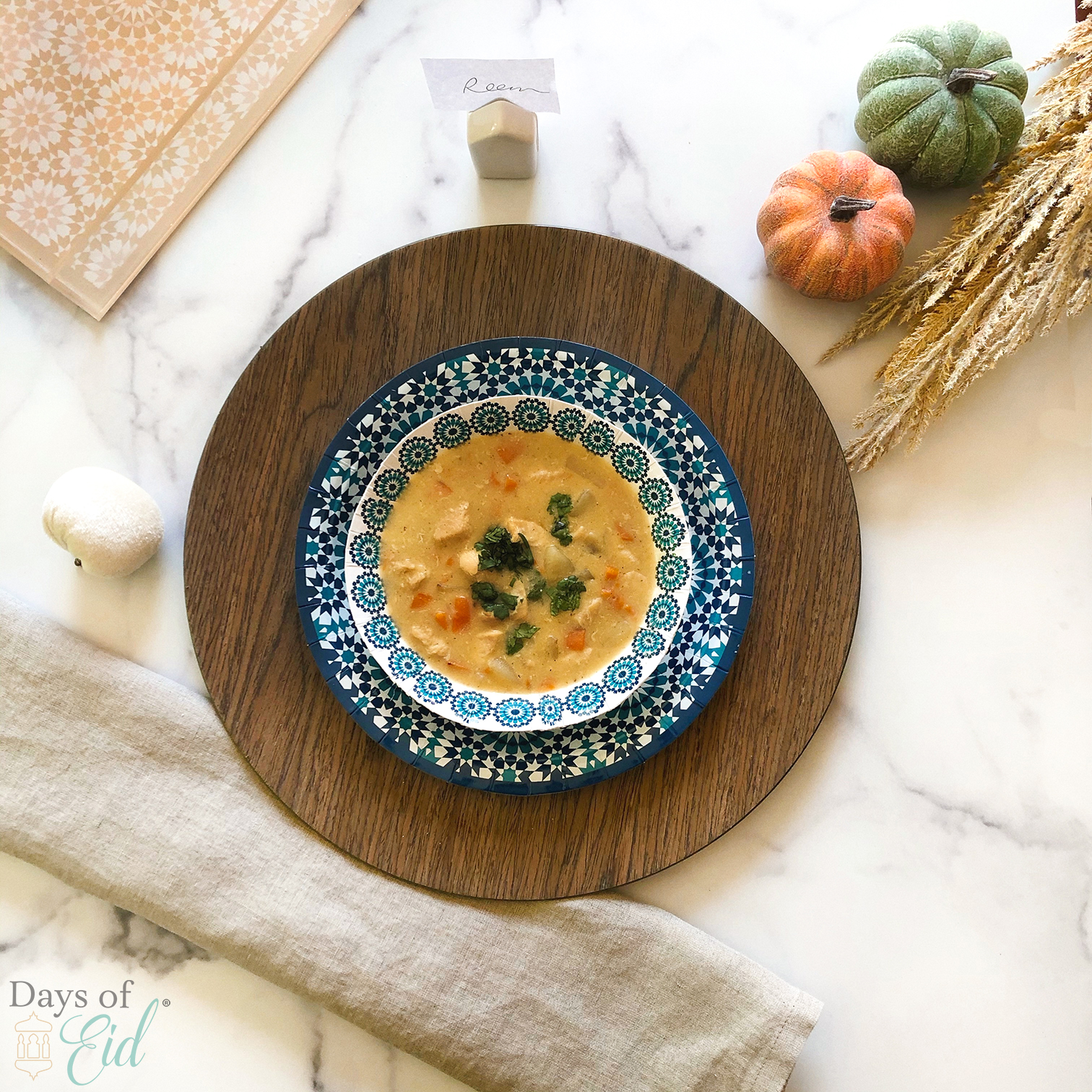Bowl of soup plated next to linen napkin and pumpkins