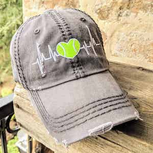 Hat with tennis ball in the shape of a heart and a heartbeat running through it