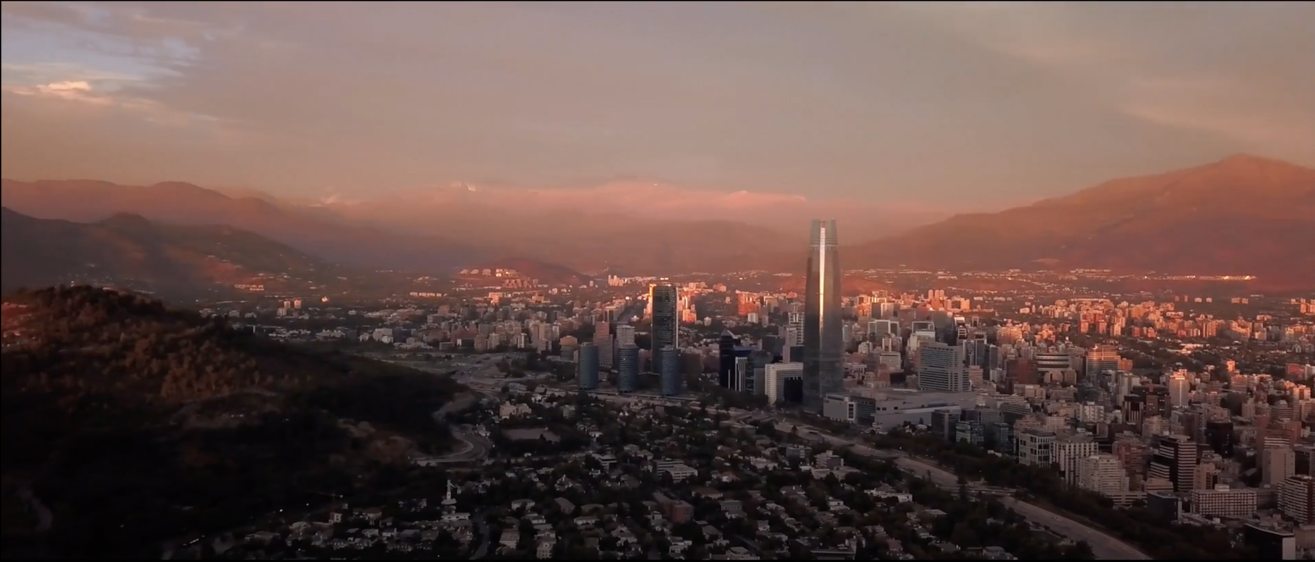Drone shot of a sunset in Santiago de Chile, In the image is the financial district and at the end The Andes