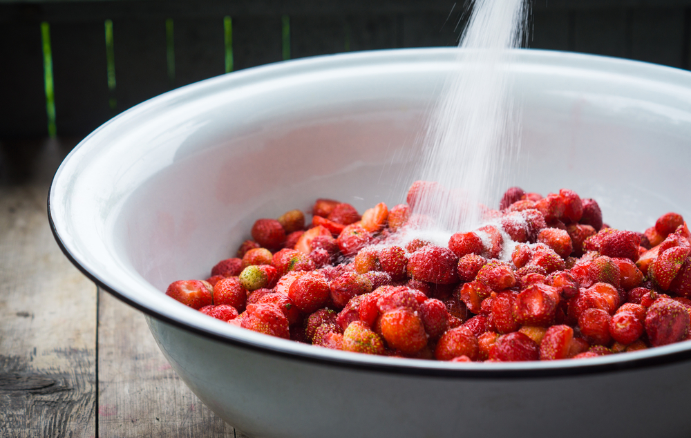 Adding sugar to strawberries for cooking jam