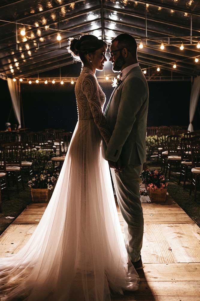 la novia y el novio mirándose a los ojos por la noche el día de su boda