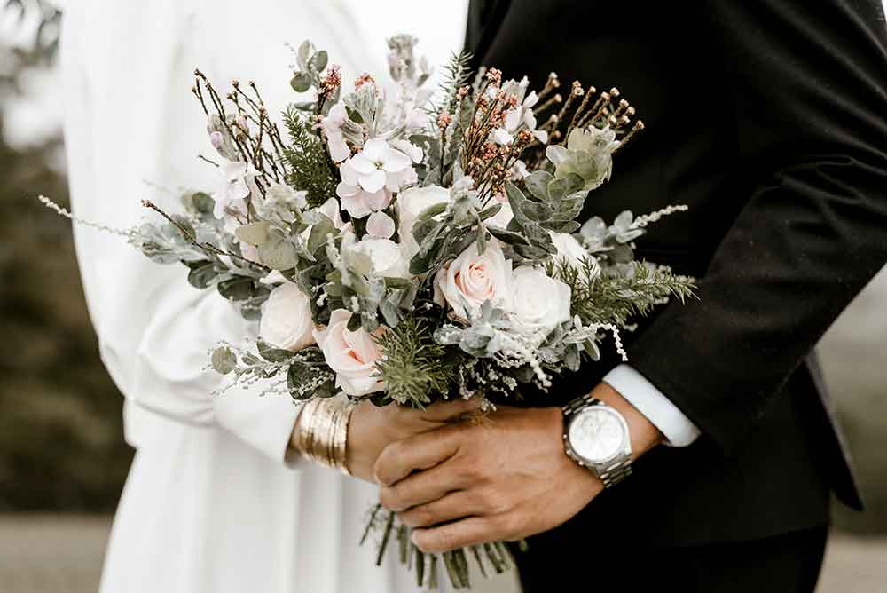 Close up of bouquet with bride and groom holding hands