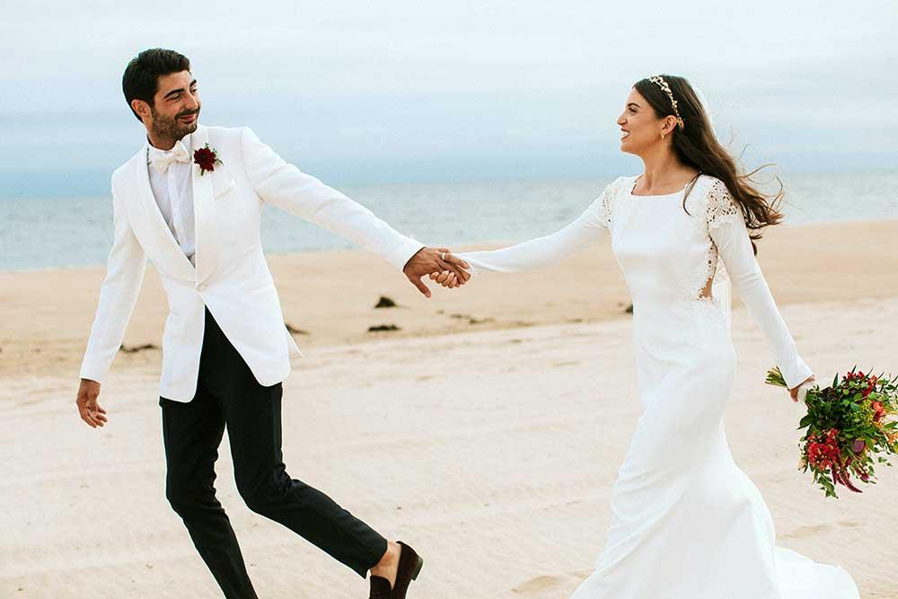 La novia y el novio en el día de su boda en la playa.