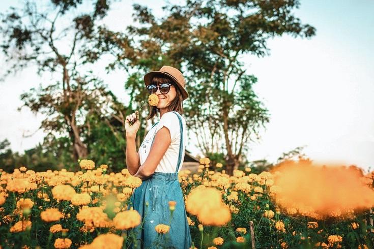 Frau mit Hut steht in einem Blumenfeld und riecht an einer Blume