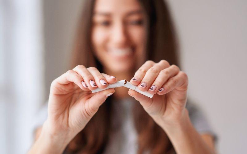 Frau mit langem Haar, dessen Gesicht nur verschwommen zu sehen ist, zerteilt eine Zigarette in zwei Teile. Ihre Fingernägel sind lackiert.