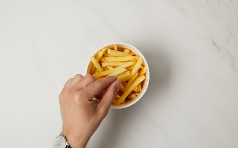 Männliche Hand mit Armbanduhr greift eine einzelne Pommes aus einer kleinen weißen Schale in der weitere Pommes liegen.