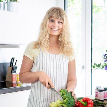 Julia Lang –Blonde Frau steht an einem Tisch und schneidet Gemüse.