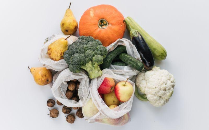Auf einem weißen Tisch liegt frisches Obst und Gemüse, darunter Kürbis, Birnen, Äpfel und Walnüsse. Diese sind zum Teil in weiß transparenten Beuteln untergebracht.