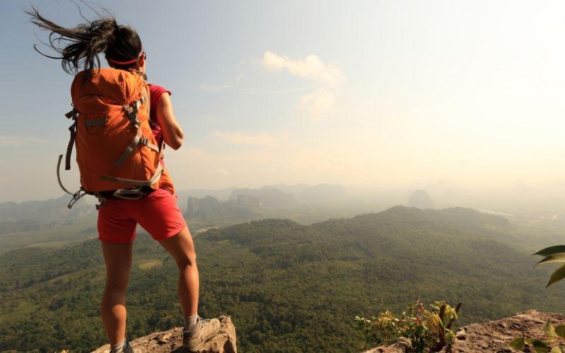 Dunkelhaarige Frau mit Rucksack steht am Felsrand auf einem Berg und schaut in die Weite. Wälder und Gebirge umgeben sie.