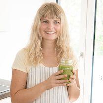 Frau steht mit grünem Smoothie an einem Tisch und lächelt