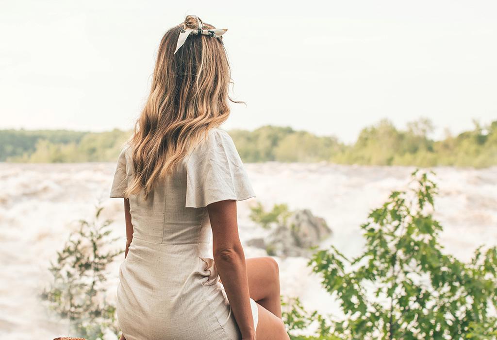 Blonde Frau sitzt auf einer Wiese und hält ihr Gesicht Richtung Sonne. Die Augen sind geschlossen und eine Hand hat sie in den Nacken gelegt. Sie lächelt.