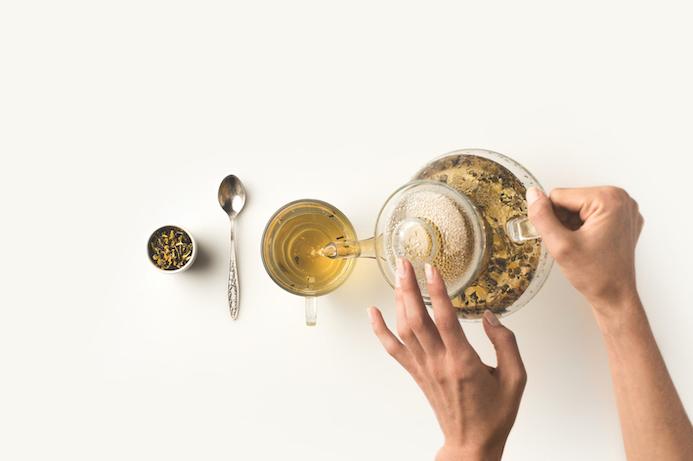 teeloeffel-teetasse-und-loser-tee-liegen-auf-einem-weißen-tisch-frauenhaende-halten-teekanne-aus-glas-und-gießen-tee-in-tasse