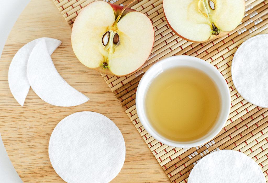 Auf einem Holzbrett, welches zum Teil mit einer Bambusmatte belegt ist, stehen kleine weiße Schälchen gefüllt mit Apfelessig, daneben liegen aufgeschnittene Äpfel.