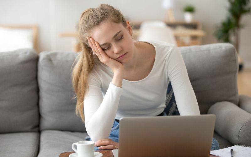 Blonde erschöpfte Frau mit fast geschlossenen Augen auf der Couch vor dem Laptop sitzen
