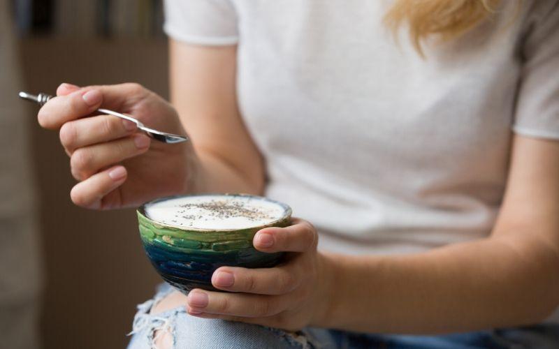 Frau hält kleine Schale mit Joghurt in der Hand. In der anderen hat sie einen Löffel.