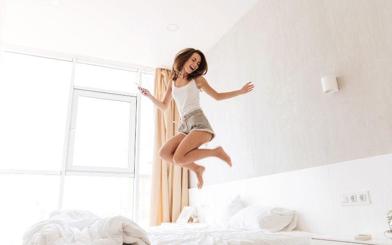 Dunkelhaarige Frau hüpft fröhlich auf einem Bett mit Kopfhörern in den Ohren