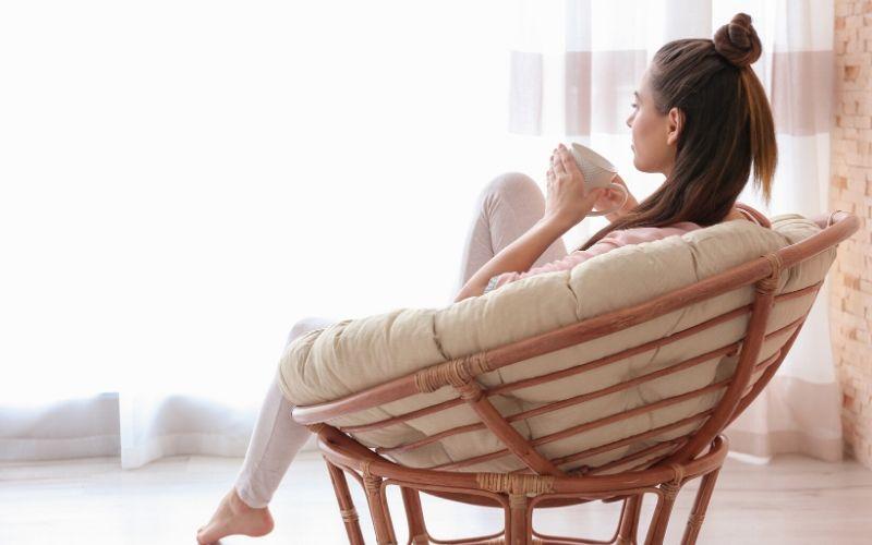 Dunkelhaarige Frau sitzt im Korbsessel mit einer Tasse Tee und sieht entspannt aus.