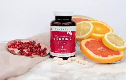 innonature-kapseldose-mit-dunkelrotem-etikett-vitamin-c-kapseln-mit-orangenscheiben-und-granatapfelkernen-auf-marmortisch-rosa-leinentuch