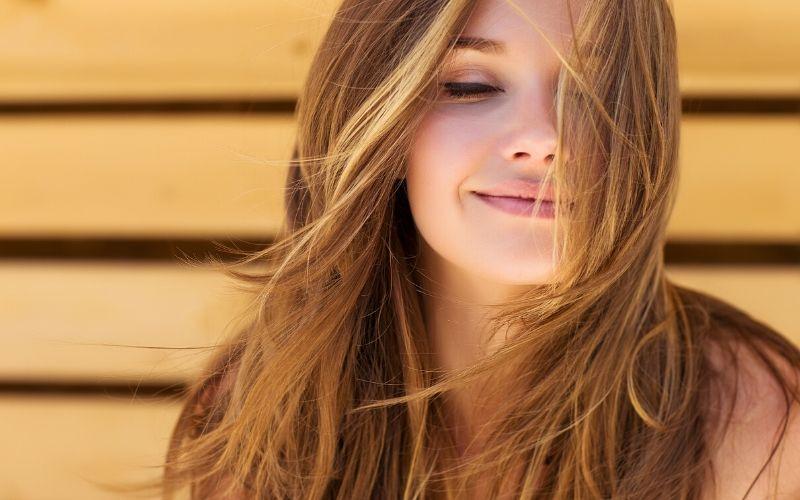 Lächelnde Frau mit langen hellbraunen Haaren, die ihr ins Gesicht fliegen vor einer gelben Wand