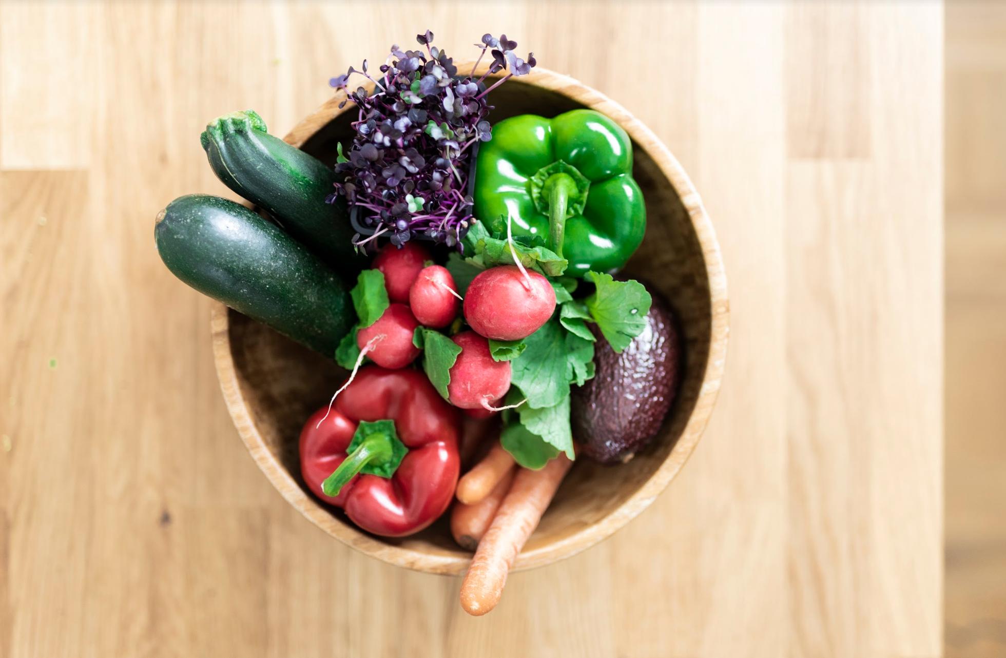 Holzschüssel mit Gemüse – paprika, Avocado, Möhren, Radieschen und Kresse –steht auf einem Holztisch