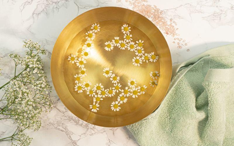 Goldene Schüssel gefüllt mit Wasser und Kamillenblüten steht auf einem Marmortisch. Daneben liegen dekorativ Blümchen und ein Handtuch in Mint.