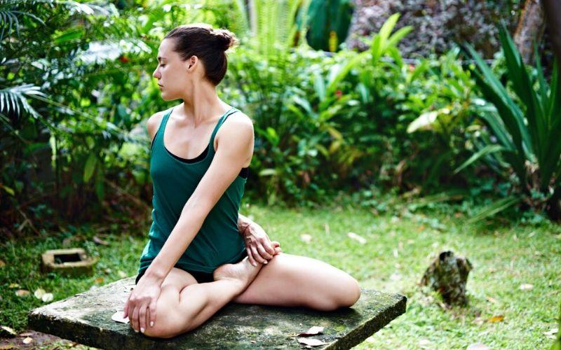Braunhaarige Frau sitzt in einer Yoga Pose im Park