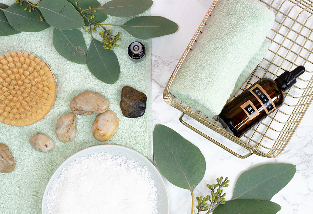 Auf einem marmorierten Untergrund sind unterschiedliche Körperpflegeartikel zu sehen. Darunter eine runde Bürste, Körperöl, mintfarbende Handtücher und ein Schälchen mit Salz. Daneben sind dekorativ Steine und grüne Eukalyptusblätter drapiert.