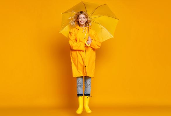 blonde-frau-mit-gelben-regenschirm-und-gelben-gummistiefeln-huepft-lachend-hoch