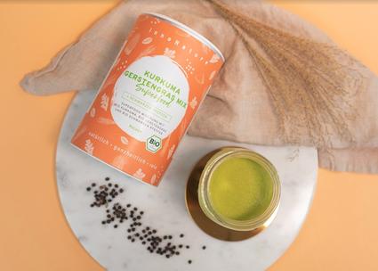 orange-shake-dose-kurkuma-gerstengras-liegt-auf-tisch-daneben-glas-gefüllt-mit-zubereitetem-drink-leicht-güne-farbe