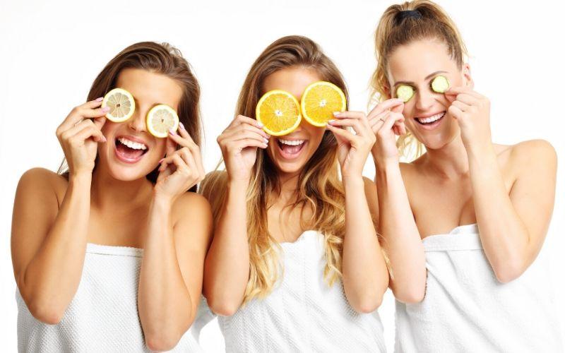 Drei Frauen mit Zitronenscheiben, Orangenscheiben und Gurkenscheiben vor den Augen.