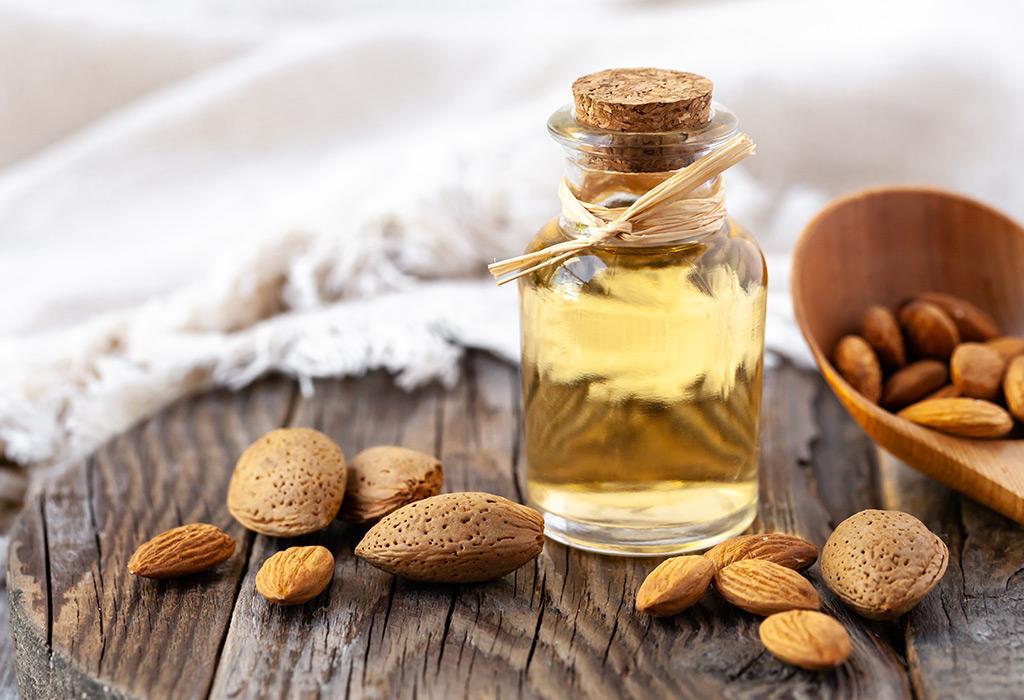 Zwei kleine Glasfläschen, gefüllt mit Öl, stehen auf einem Holztisch. Dahinter sind Äste eines Olivenbaums und Blätter zu sehen.